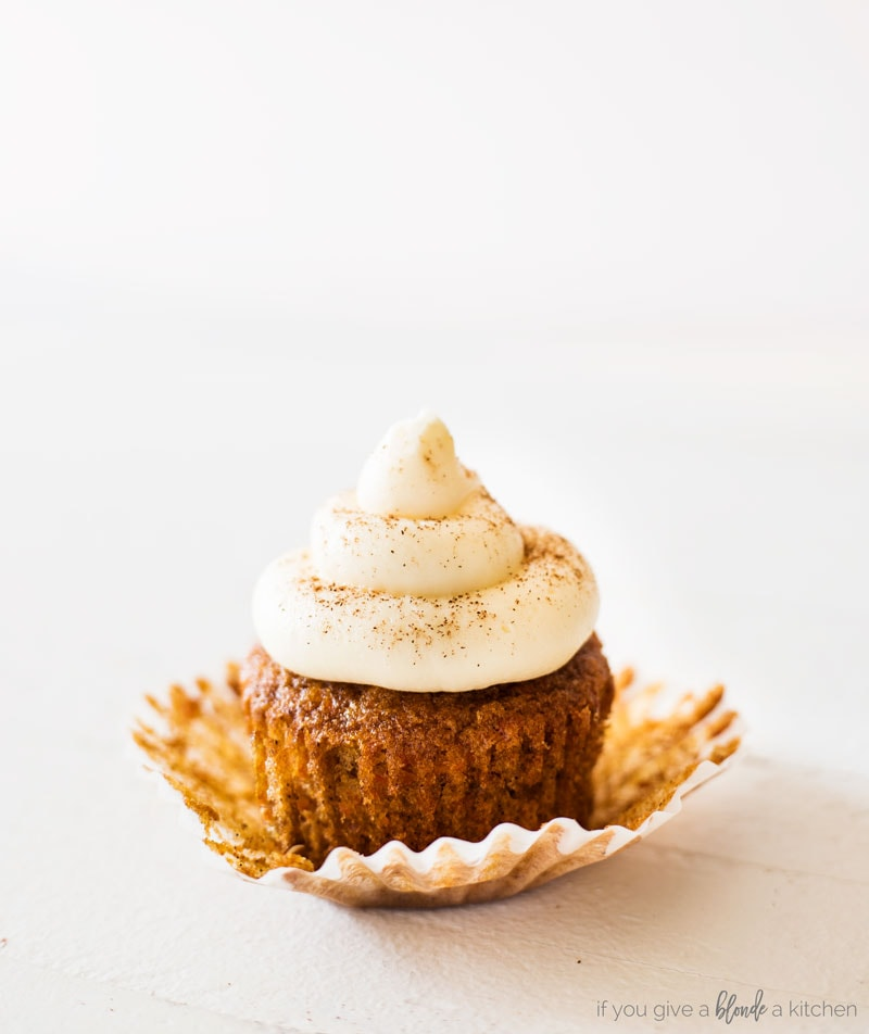 Carrot cake cupcakes with cream cheese frosting. Cupcake sitting on top of open paper liner. Frosting dusted with cinnamon
