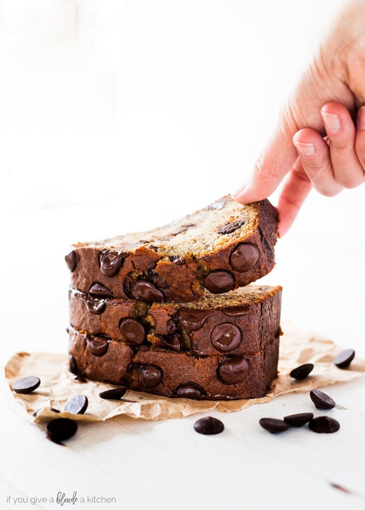 Chocolate chip banana bread recipe hand reaching for slice of banana bread with melted chocolate chips