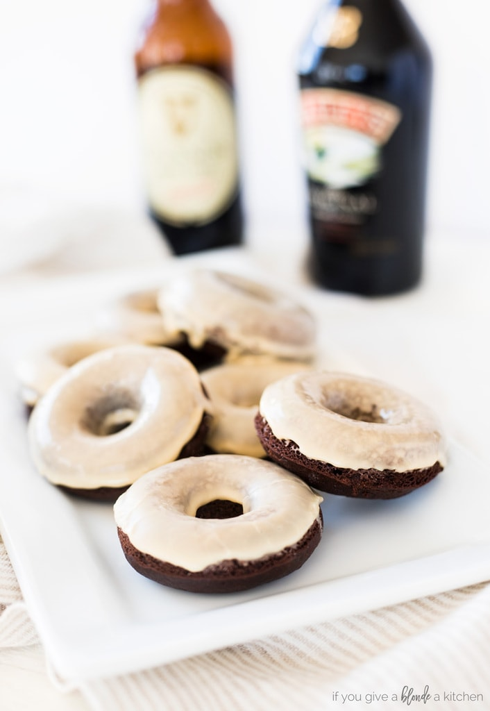 guinness chocolate donuts with baileys irish cream glaze on white plate with light striped kitchen cloth. Bottle of stout beer and Baileys in white background
