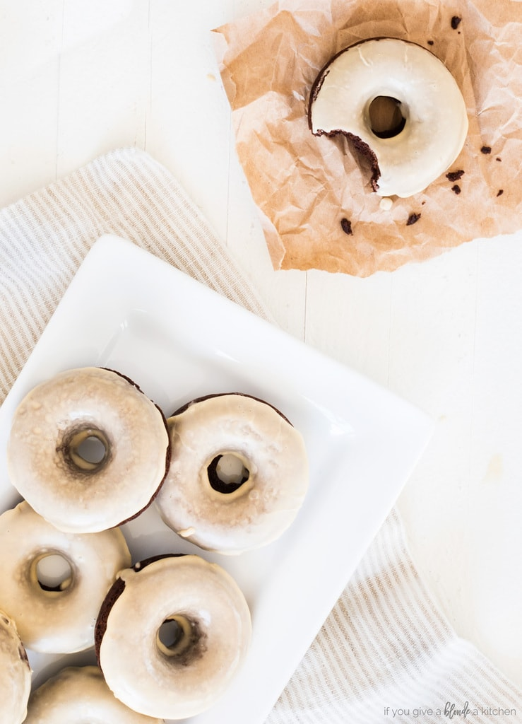 guinness chocolate donuts on plate with izing. Donut with bite removed and crumbs on brown baking paper. White wood background