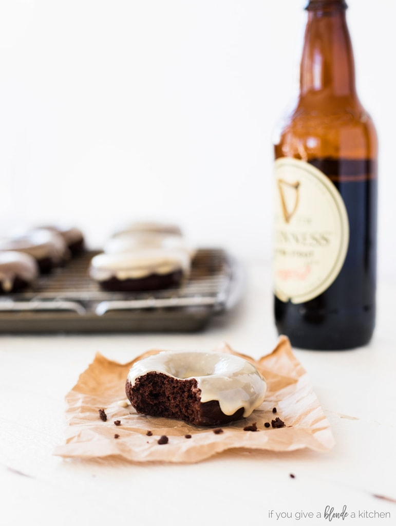 guinness chocolate donuts with stout beer bottle. Donut with a bite on brown baking paper . Donuts on wire cooling rack in the background with glaze