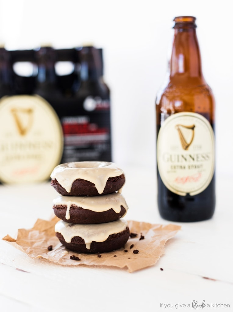 guinness chocolate donuts with bottle of stout beer, stack of three glazed chocolate donuts on brown paper with white wood table