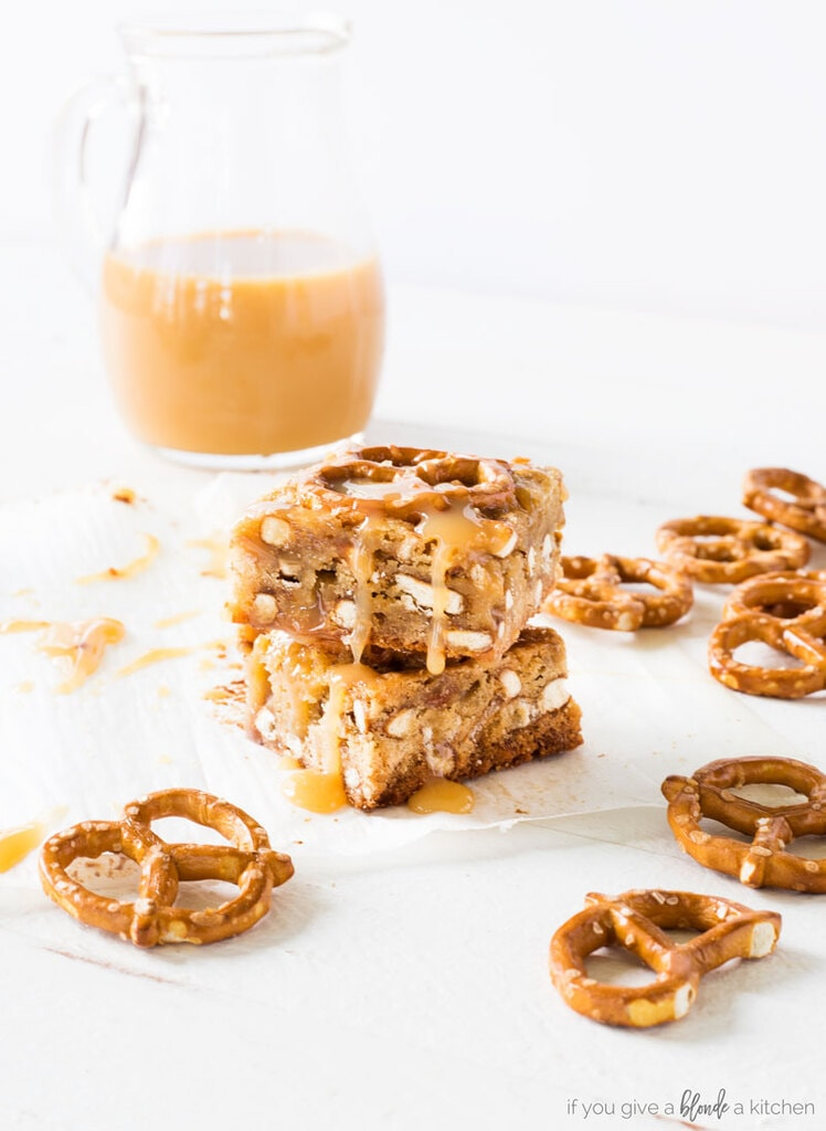 salted caramel pretzel blondies. mini pretzel twists. caramel in pouring pitcher. white background. blondies stacked on top of each other