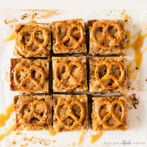 salted caramel pretzel blondies. square blondies with mini pretzel twists on top. symmetry with white background and drizzle of caramel