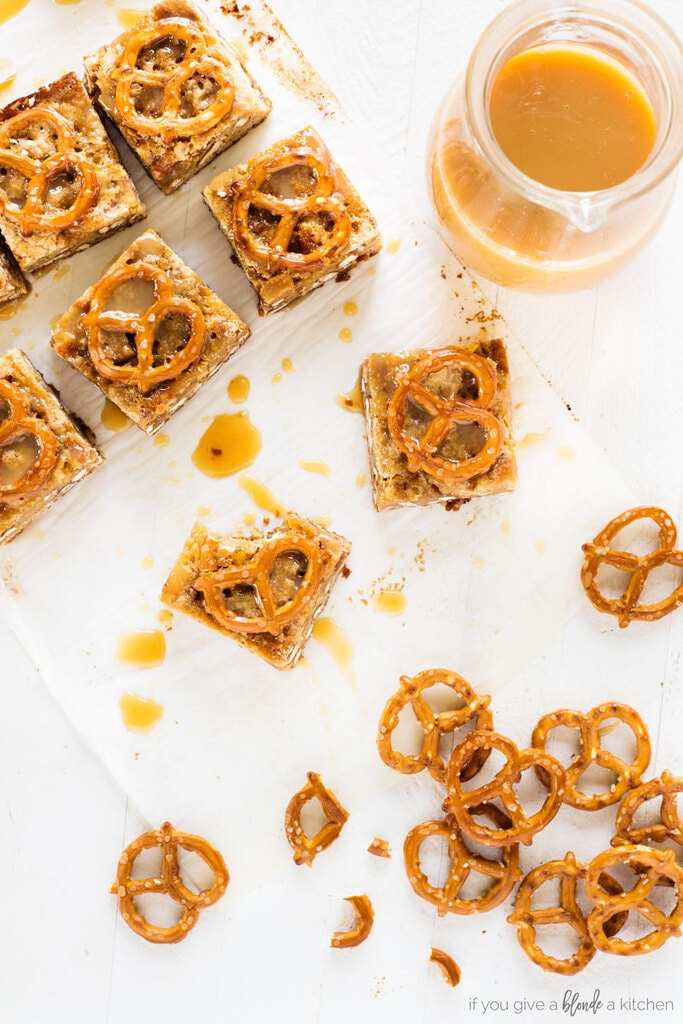 salted caramel pretzel blondies cut into squares. Mini pretzel twists and caramel sauce