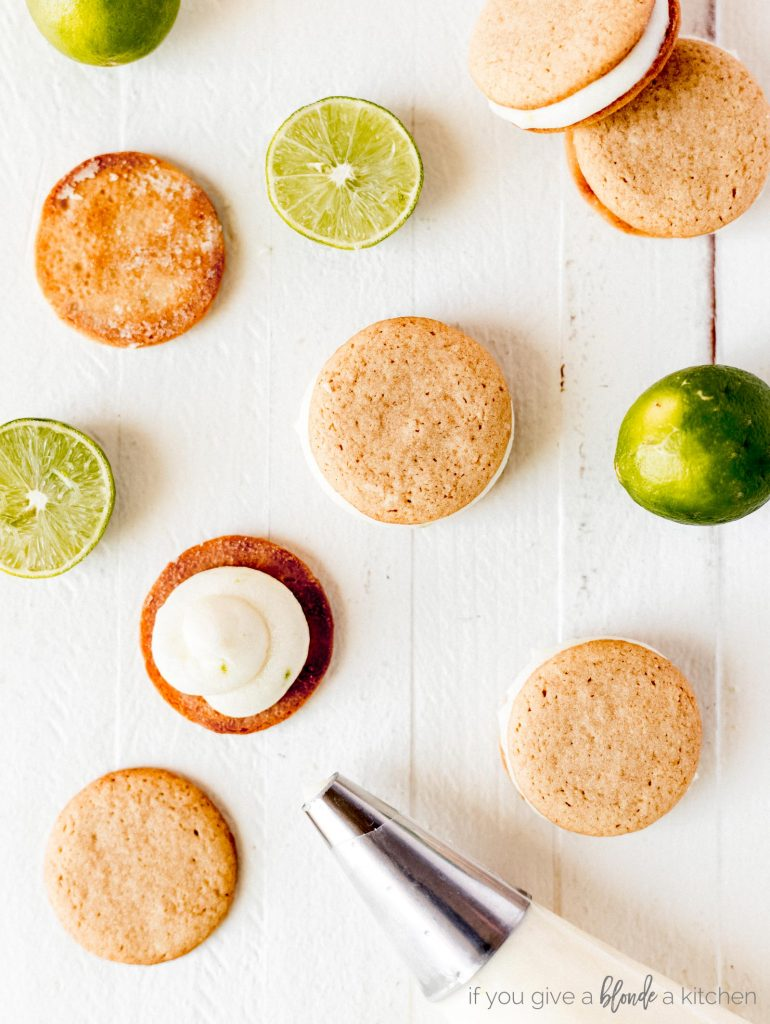 key lime pie cookies with cream cheese frosting, round graham cracker cookies, key limes on white wood background