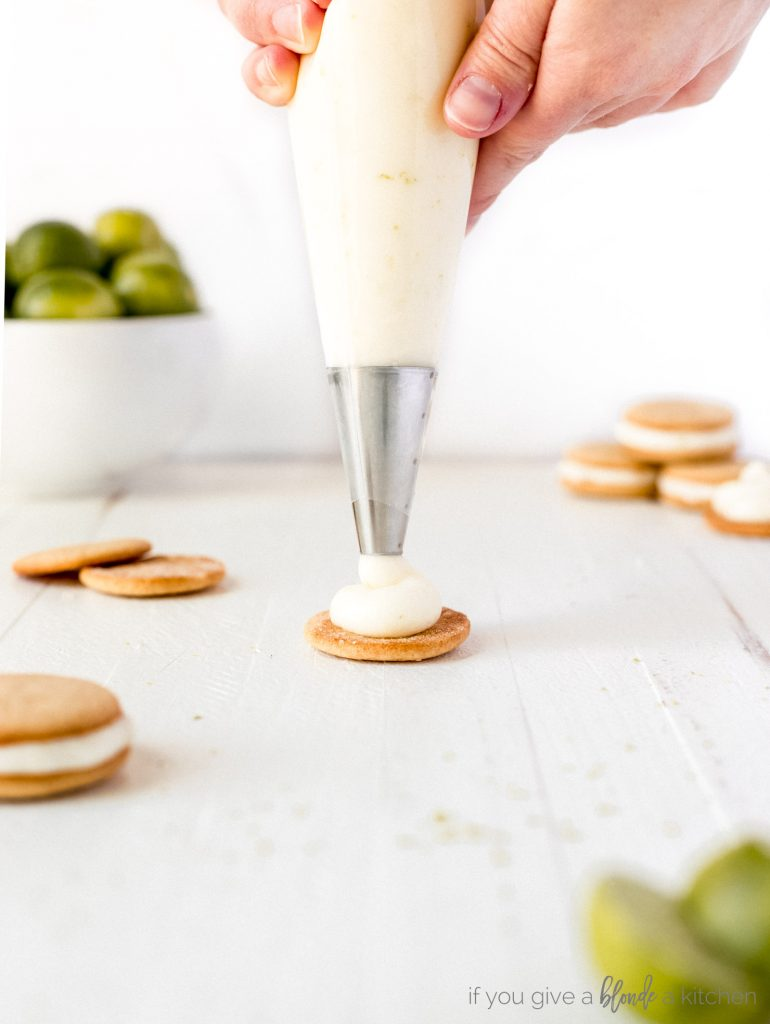 key lime pie cream cheese frosting being piped onto a graham cracker cookie