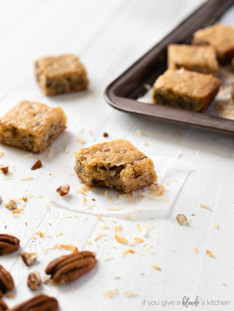 pecan coconut blondies with bite, cookie sheet in background with square barsz