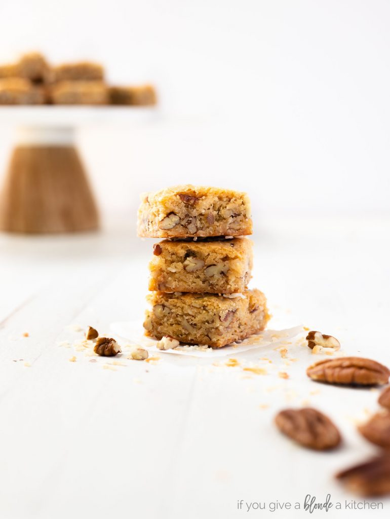 pecan coconut blondies stacked on top of each other showing center of the dessert bars. Cake stand in the white background, pecans in the foreground