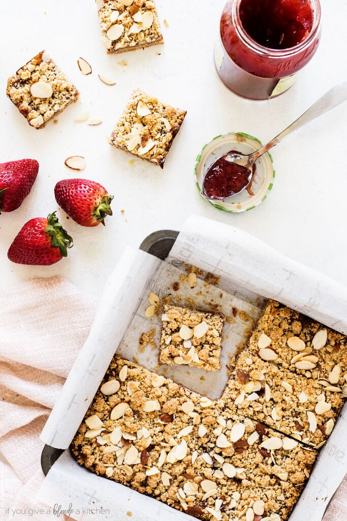 strawberry oat bars are baked in a 8x8 inch pan with topped with slivered almond flour crumble