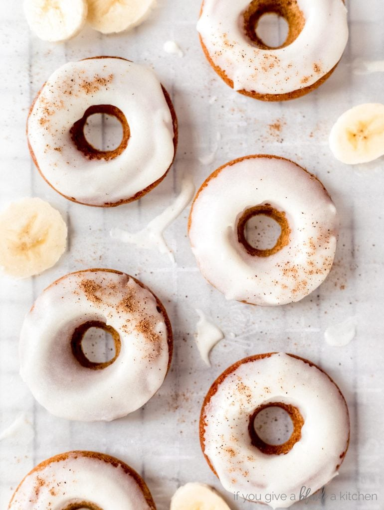 brown butter banana donuts with icing and sprinkle of nutmeg laid flat on parchment paper with banana slices