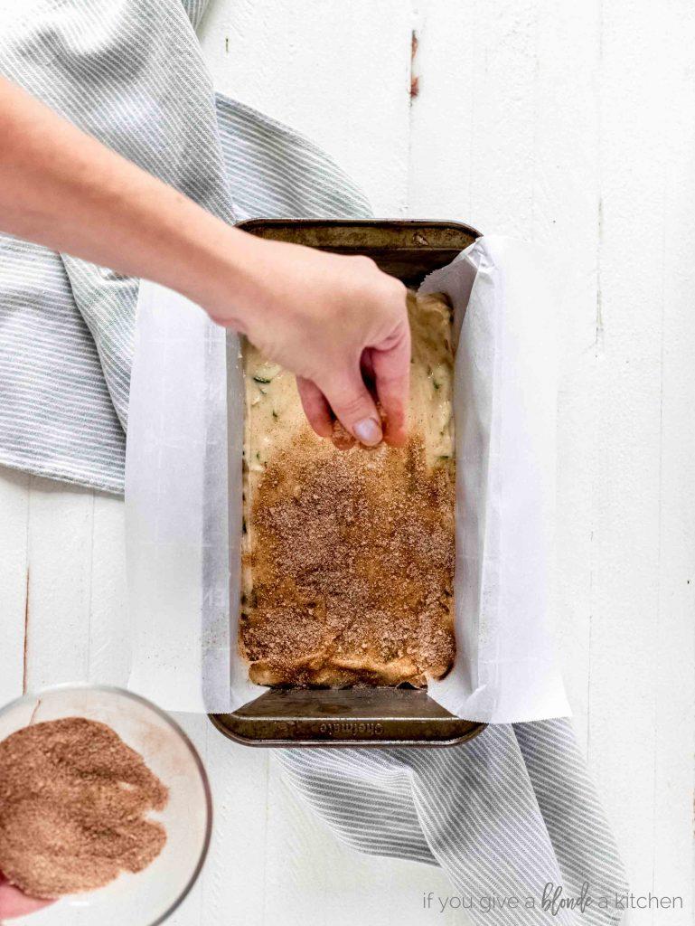 cinnamon sugar sprinkled on top of cake batter in a 9x5 loaf pan