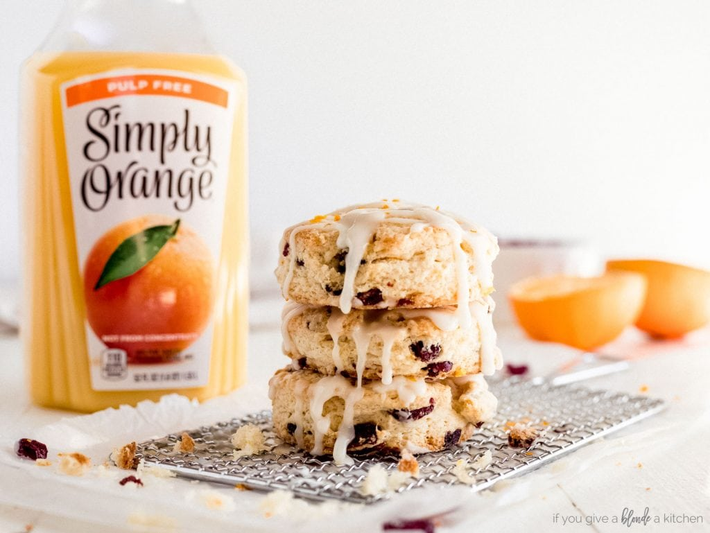 stack of cranberry orange scones with bottle of orange juice