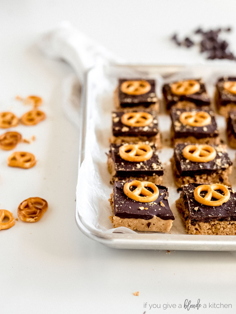 peanut butter pretzel bars on wax paper on baking sheet