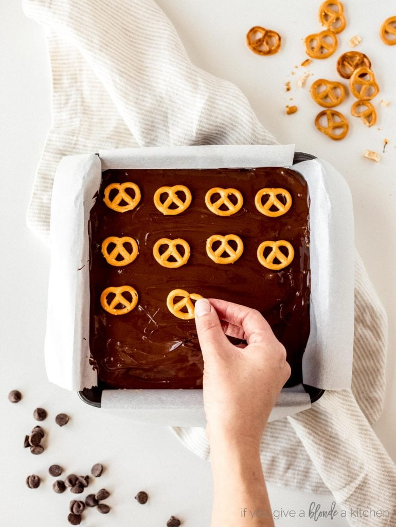 step by step mini pretzels being placed on top of melted chocolate layer