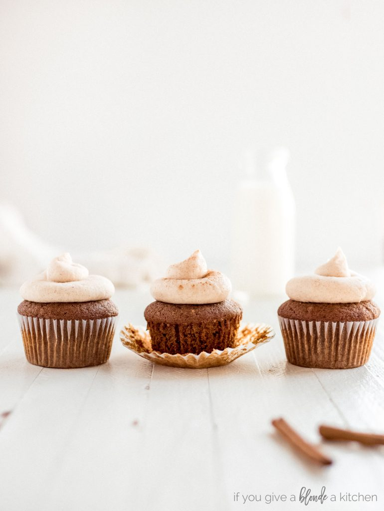 three cupcakes in a row with cinnamon frosting
