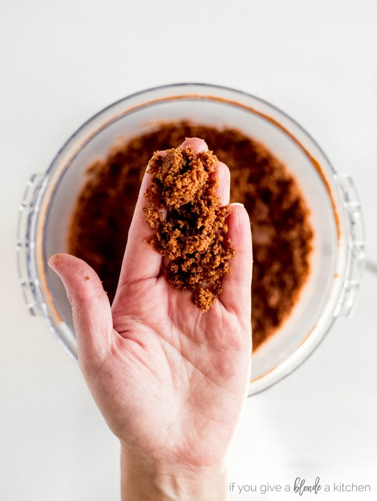 hand holding gingersnap crust mixture