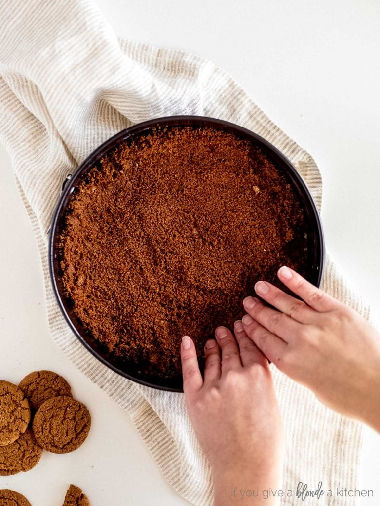hands pressing gingersnap crust into a springform pan