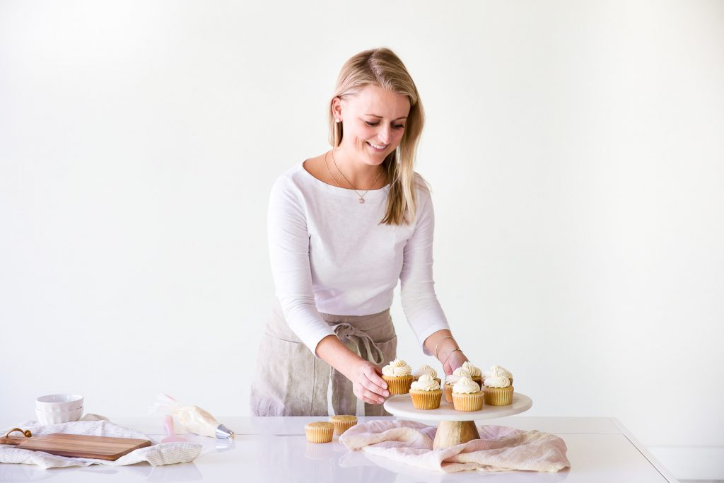 haley baker placing vanilla cupcakes on marble cake stand