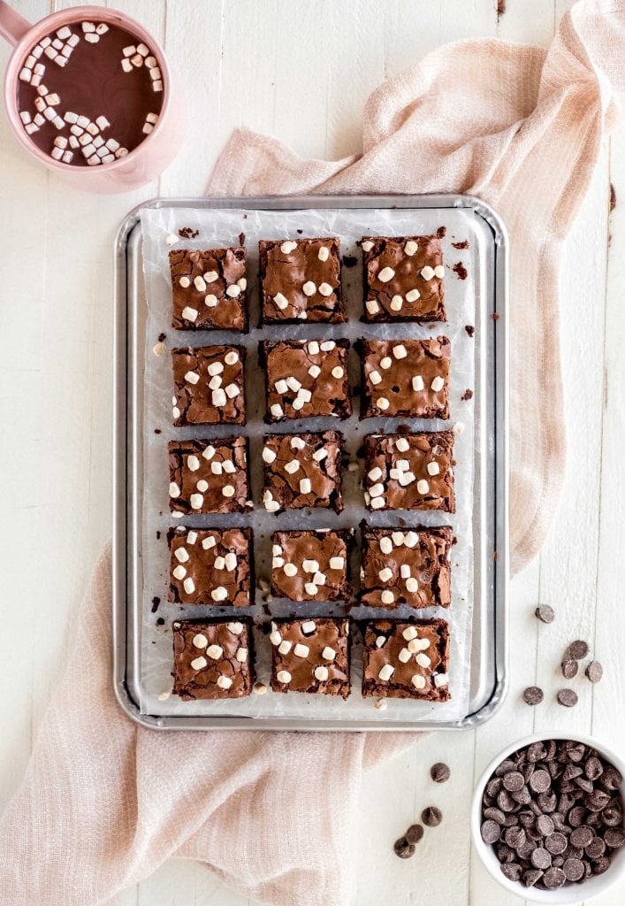 brownies with mini mallows cut into squares on baking sheet. Bowl of chocolate chips and mug of hot cocoa