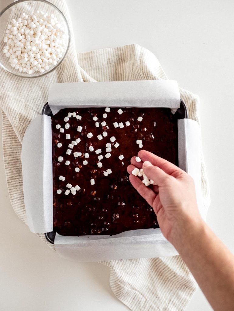 hand sprinkling mini marshmallow bits on to hot chocolate brownies in 8x8 pan