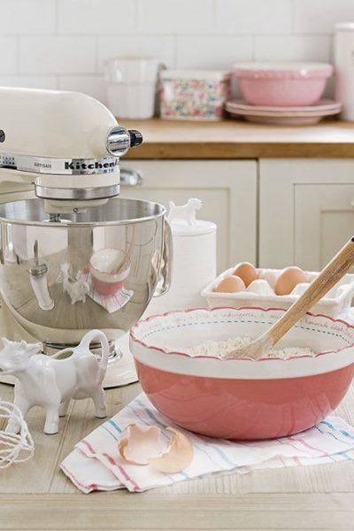 white kitchenaid mixer with pink mixing bowl on counter