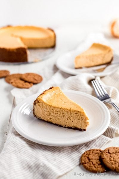 pumpkin cheesecake slice on white plate with gingersnap cookies
