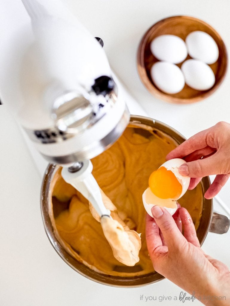 stand mixer with hands cracking egg