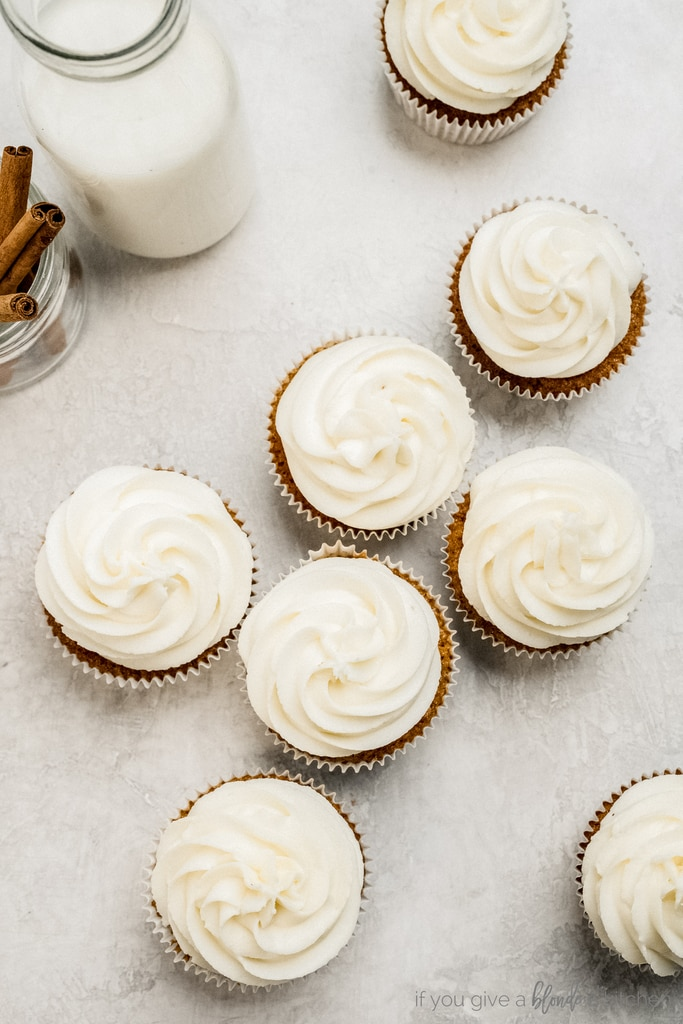 cream cheese frosting on top of cupcakes with glass of milk and cinnamon sticks