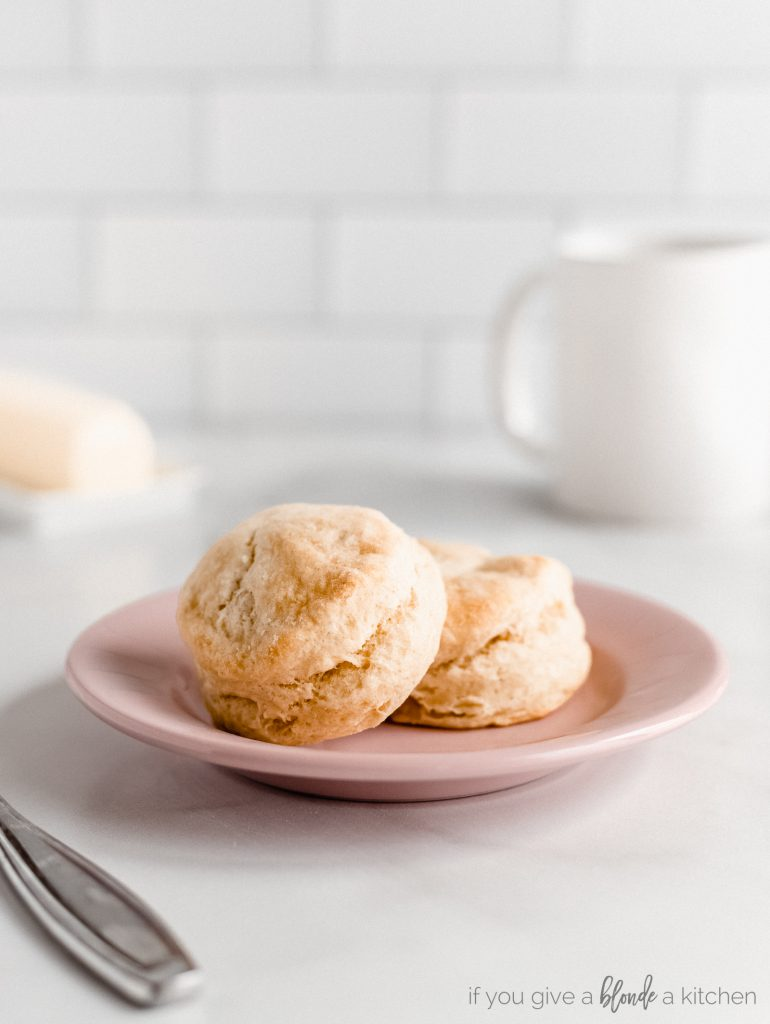two buttermilk biscuits on round pink plate