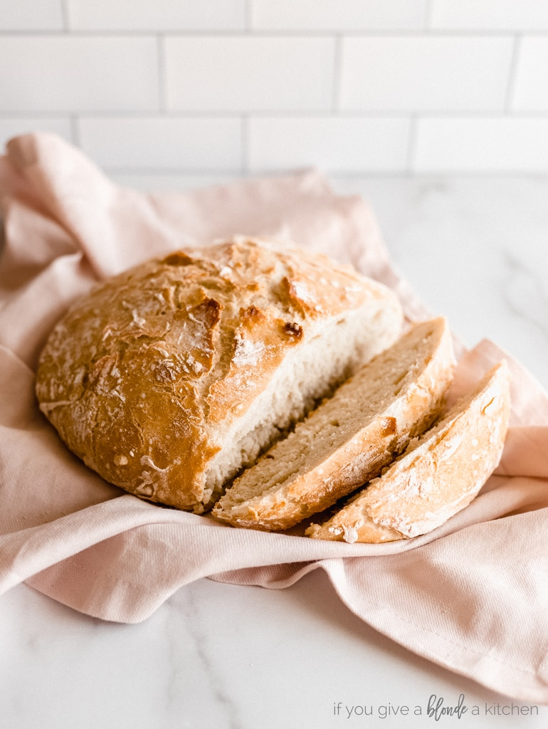 artisan bread with two slices removed on pink kitchen towel