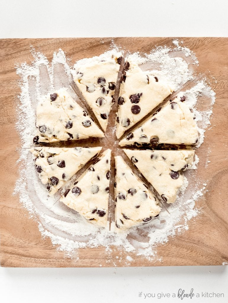 chocolate chip scone dough cut into triangles on floured work surface