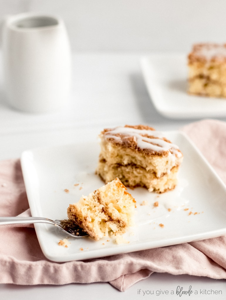 coffee cake square on plate. Fork holding bite of coffee cake