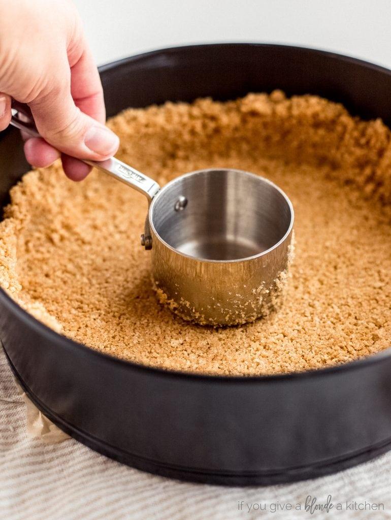 hand pressing stainless steel measuring cup on graham cracker crust in springform pan
