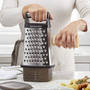 woman shredding parmesan cheese on box grater