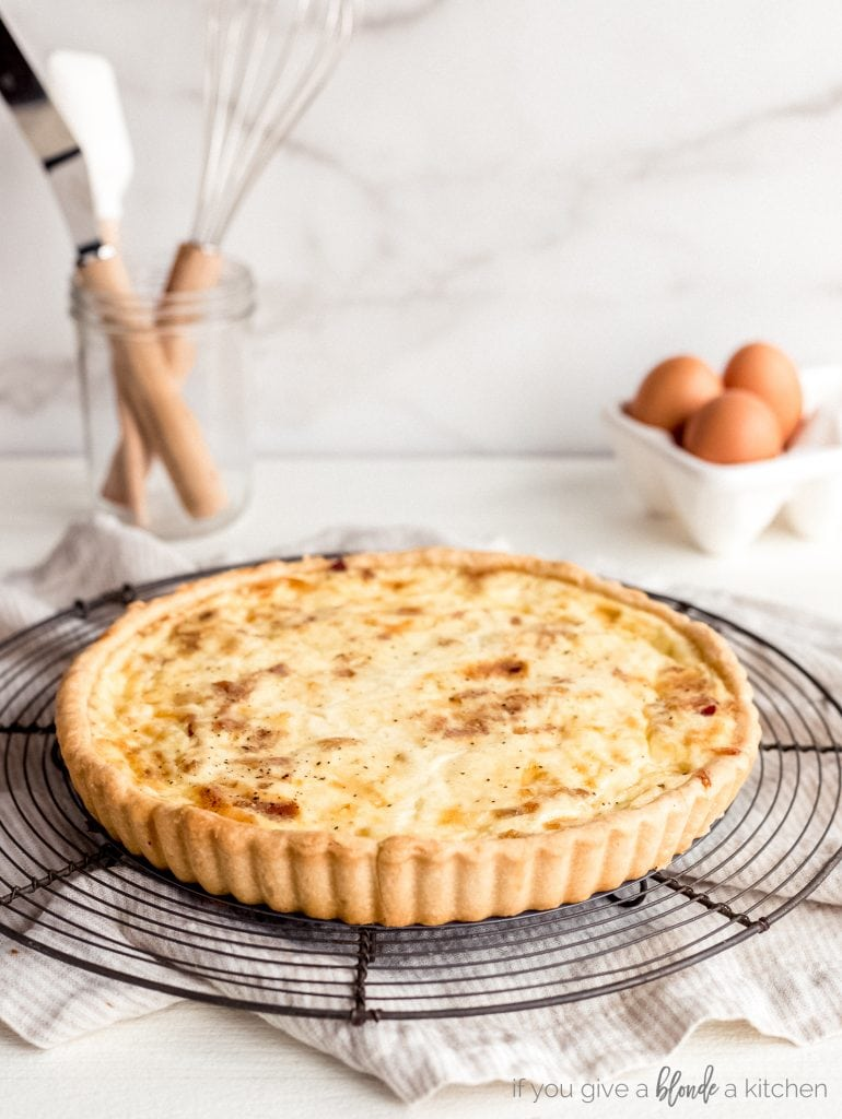 quiche lorraine on round wire cooling rack on countertop
