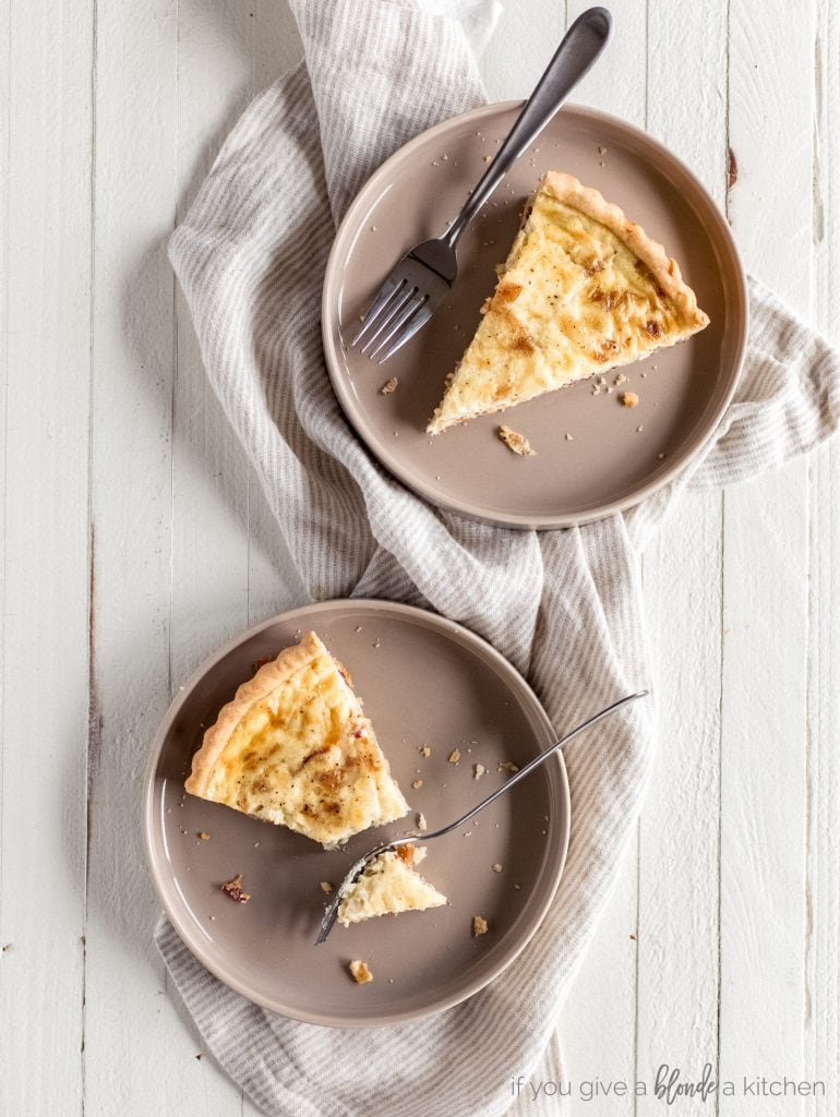 two slices of quiche on round plates with forks