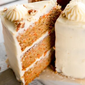 triple layer carrot cake slice with cream cheese frosting taken out of cake