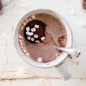 hot chocolate bomb with mini marshmallows floating on top of hot chocolate in mug