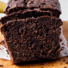 slice of chocolate zucchini banana bread leaned up against loaf