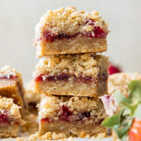 stack of three strawberry oatmeal bars next to a fresh strawberry